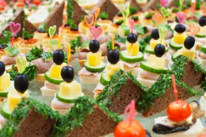 a lot of canapes with skewers on a buffet table